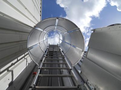 Echelle a crinoline en aluminium avec sortie haute de face, porte de condamnation d'accès et tôle perforée