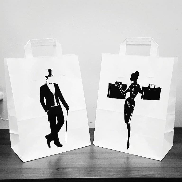Paper bags with flat handles are made on white craft.