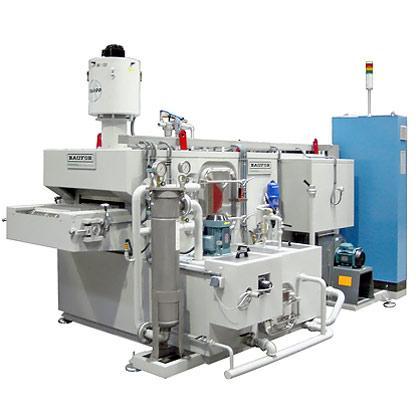 Lavadora industrial con cinta transportadora para la limpieza y desengrase de piezas en continuo.