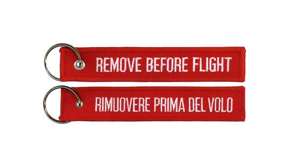 Embroidered Keyholder Remove Before Flight with red fabric and red merrow border. Size 130x30 mm. Keychain with different logo on back side Rimuove Prima del Volo for Italian market. Send your logo.