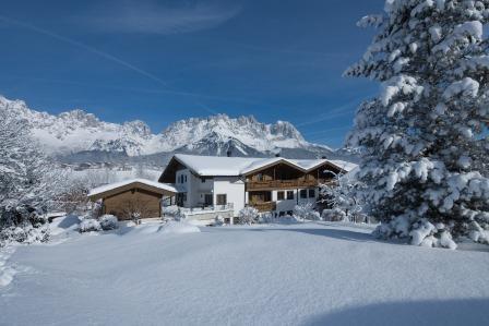 Die Ferienwohungen im Winter 2010 mit dem Wilden Kaiser im Hintergrund.