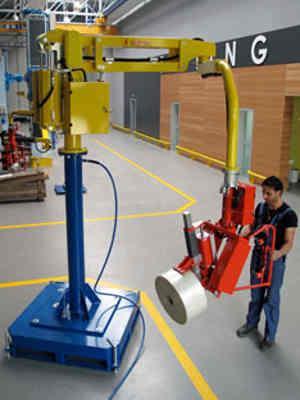 Manipulateur industriel modèle PEC sur colonne autostable équipé d'un outil à mandrin à expansion pour la prise et le basculement de bobines – un doigt de maintien permet d'éviter l'effet de télescope