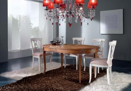 Tavolo ovale allungabile con apertura al centro, dotato di 2 allunghe da cm 50. Piano realizzato in legno di noce intarsiato e gambe in massello di faggio.