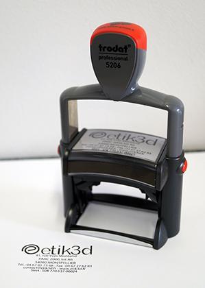 Exemple de tampon de société avec son logo, monté sur un Trodat Professionnel 5206 à armature métallique. Informations type transmises : adresse, SIRET, contacts et image de l'entreprise via le logo.