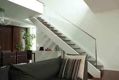 Escalier en bois laqué avec double support latéral et marche en wengué. Garde-corps en verre profilé en inox en forme de « U ». Fixation invisible.