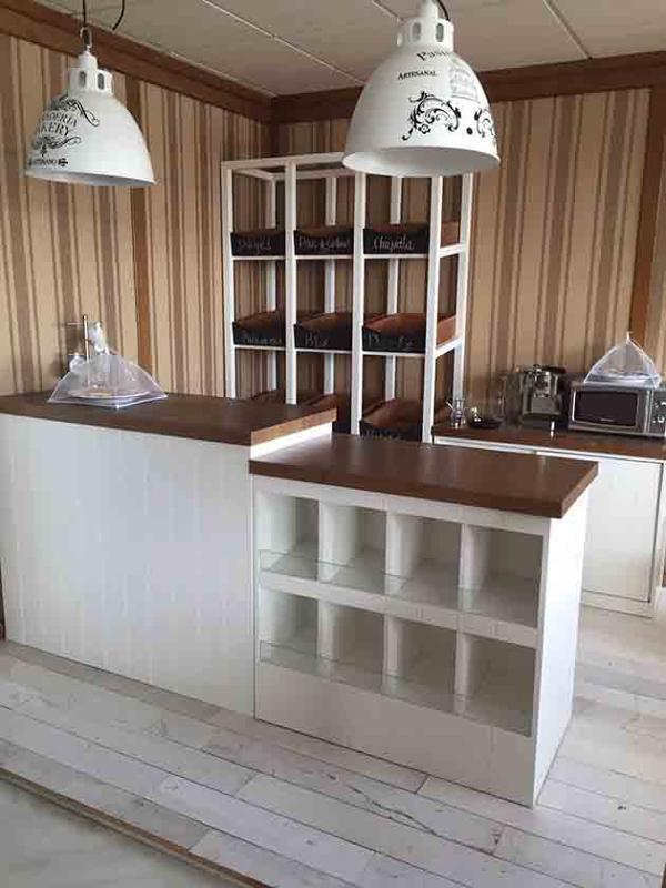 En madera, ranurada y lacada en blanco, estilo vintage. Mostradores y estantes con cajoneras para pan.