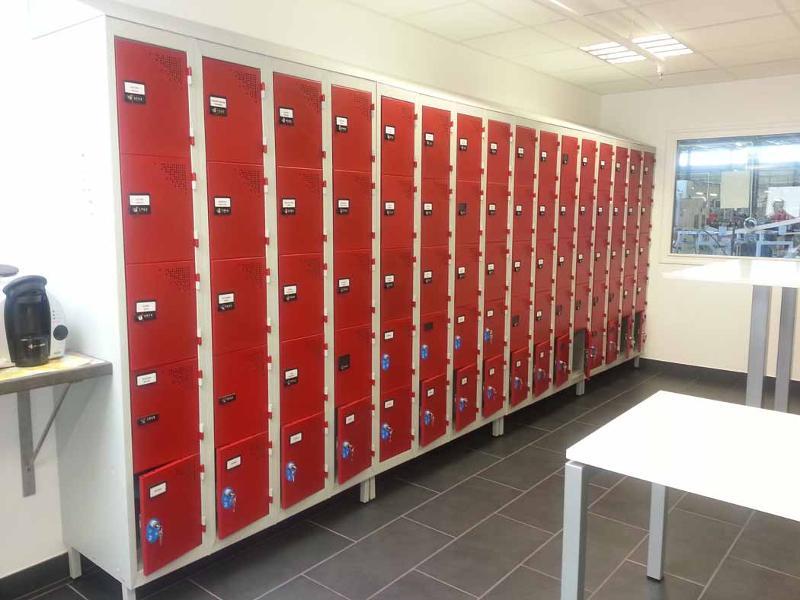 Exemple d'une installation de vestiaires multi casiers avec serrures à code, montés sur pieds et munis de coiffes pour la sécurité.