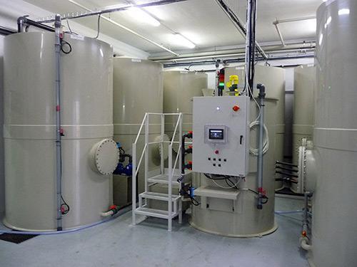 Installation de traitement des eaux usées avec la station de recyclage et les cuves d'eau usée et d'eau claire. Dans cette réalisation, les eaux traitées sont chargées en colle et en encre.