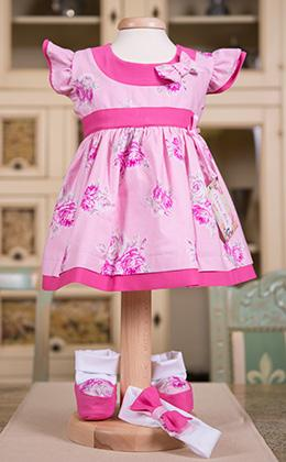 An adorable 100% cotton dress with floral print, ruffled sleeves are two overlapping material, and printed cotton and cotton knit waist has a belt that connects to the back.