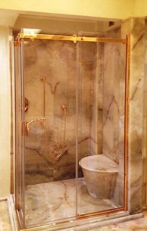 Progettazione e realizzazione di box doccia con struttura in ottone dorato e cristalli temperati e stratificati