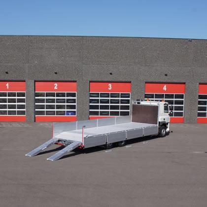De foto laat een zwaar uitgeruste open carrosserie zien. Deze is verwerkt met robuuste aluminium vloer en versterkte oprijplaten. Daarnaast is de open laadbak voorzien van op maat RVS zijkisten.