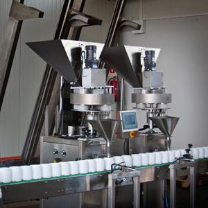 Ilustracja przedstawia maszynę w trakcie konfekcjonowania proszków.