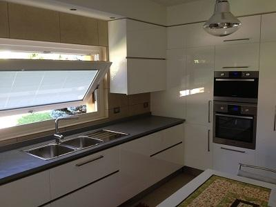 Kitchen with white parapan doors and gray quartz top