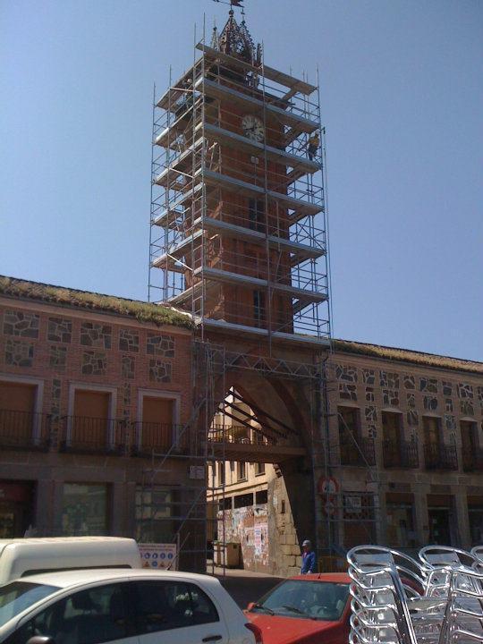 Montaje de andamio multidireccional elevado sobre arco de torre de Reloj en Oropesa dejando paso para vehiculos por su interior.