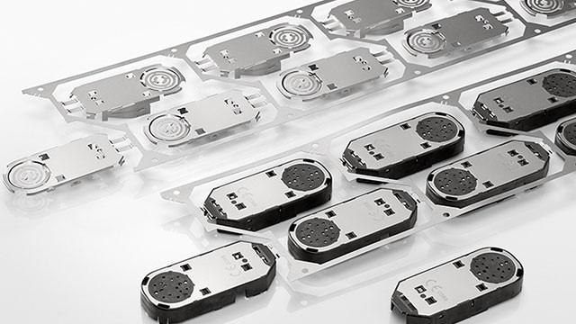 Compositing stamped metal insert parts and plastic -