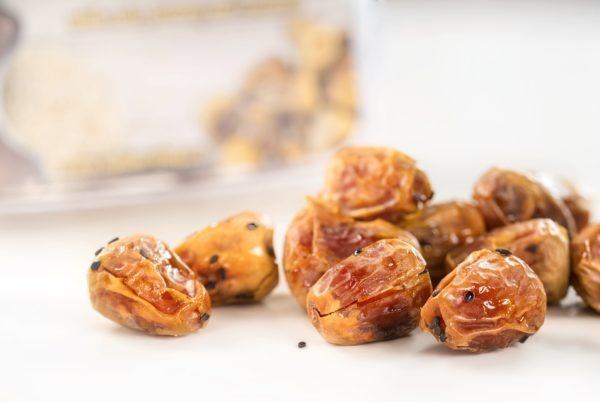 Sukkari dates with hazelnuts in honey with sesame sprinkling -